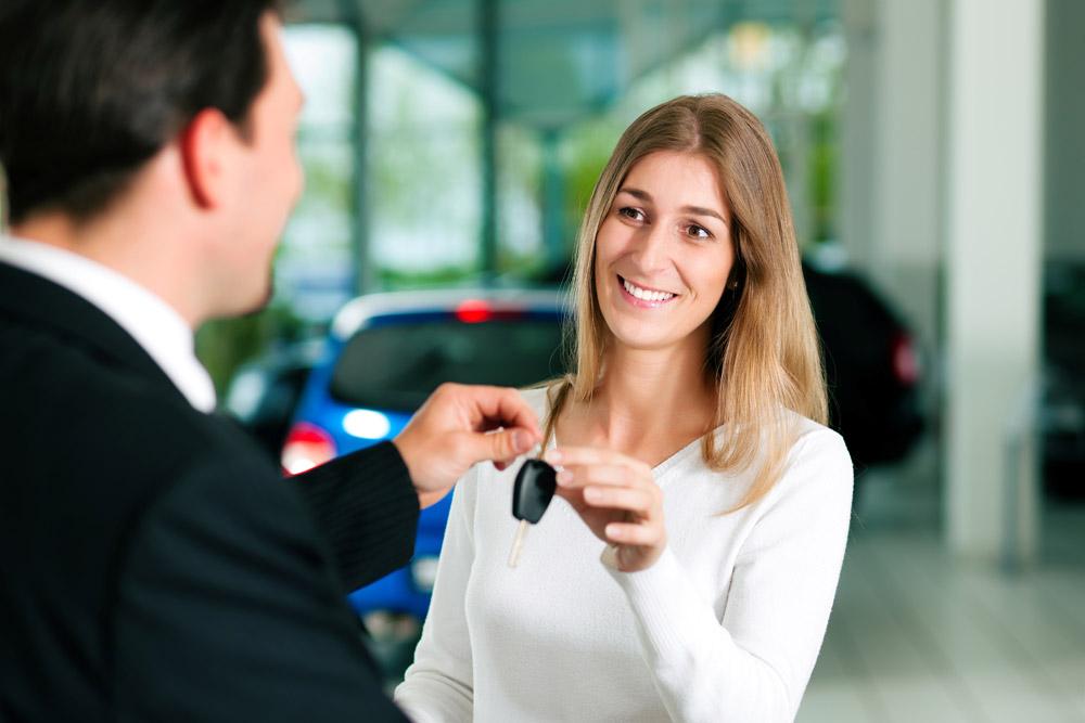 woman car shopping buying leasing at car dealership keys