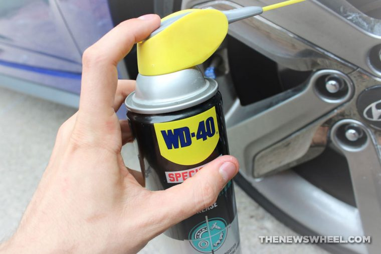 A can of WD-40 being sprayed onto a car wheel