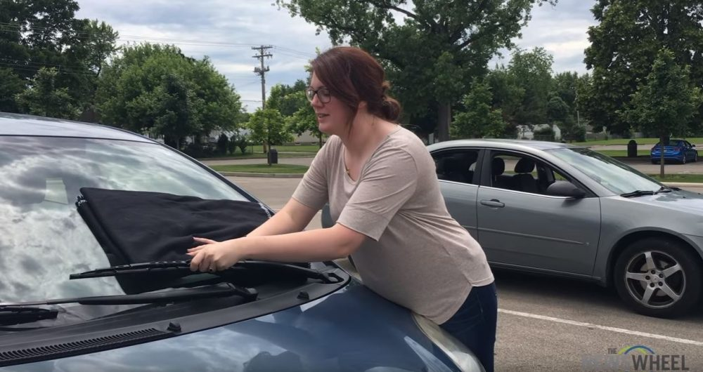 Woman putting a blanket on a car windshield under the wipers in order to install new wiper blades