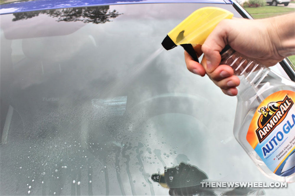 glass cleaner on car windshield spraying off dirt