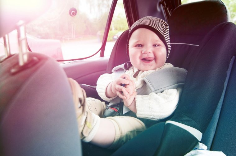 happy baby in car seat with hat