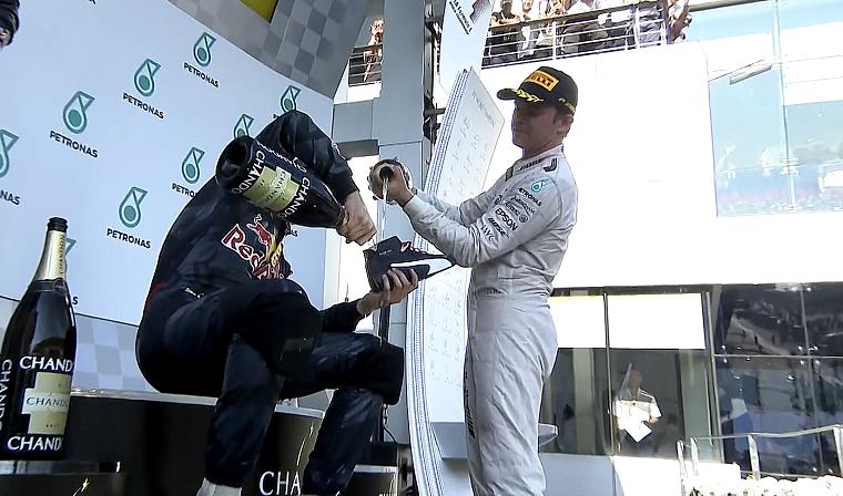 Nico Rosberg helps Daniel Ricciardo prepare a shoey.