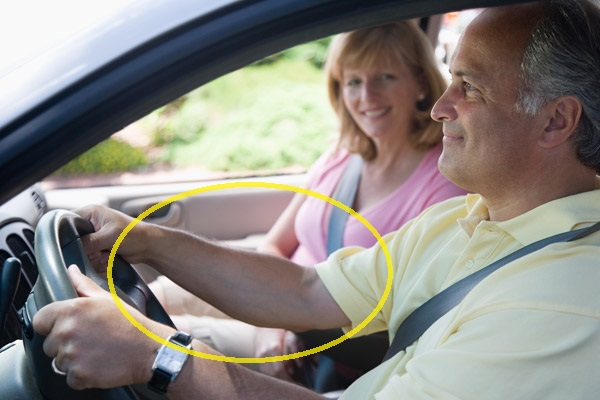 Man and woman in car together. Driver has arms outstretched.
