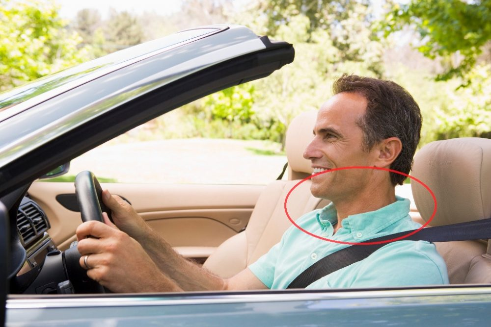 Smiling driver in car does neck exercises