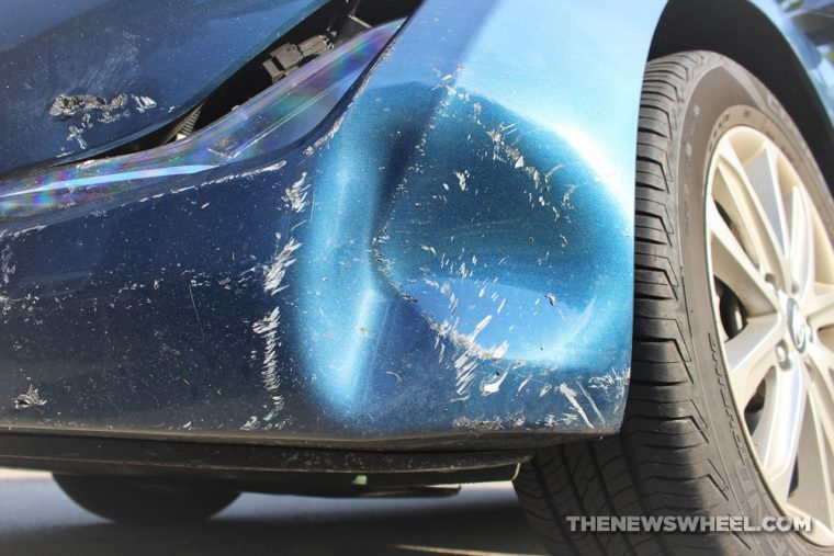 A car's rear bumper with a dent in it from a collision