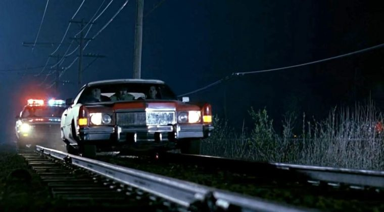 Groundhog Day movie cars Cadillac Eldorado driving on train tracks
