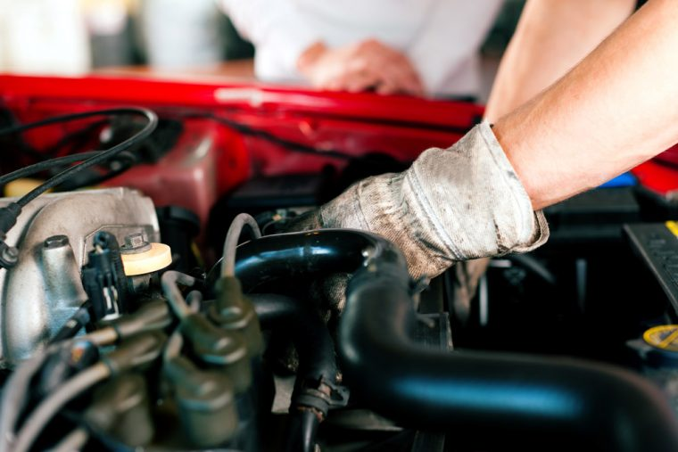 mechanic wearing a glove and working on a car engine