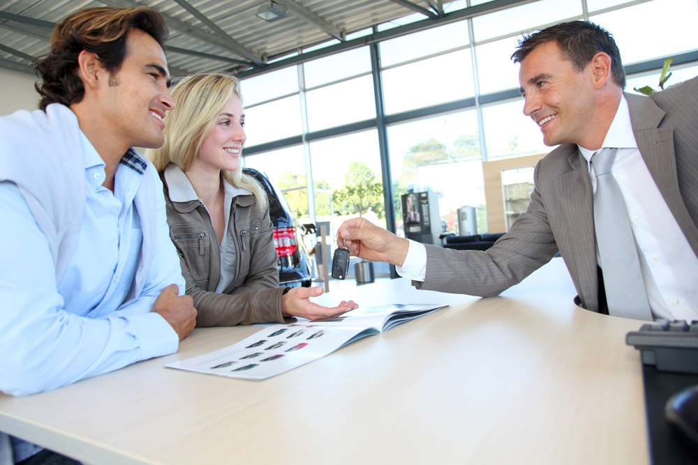 Man and woman shopping for new car at dealership with salesman discuss auto financing options
