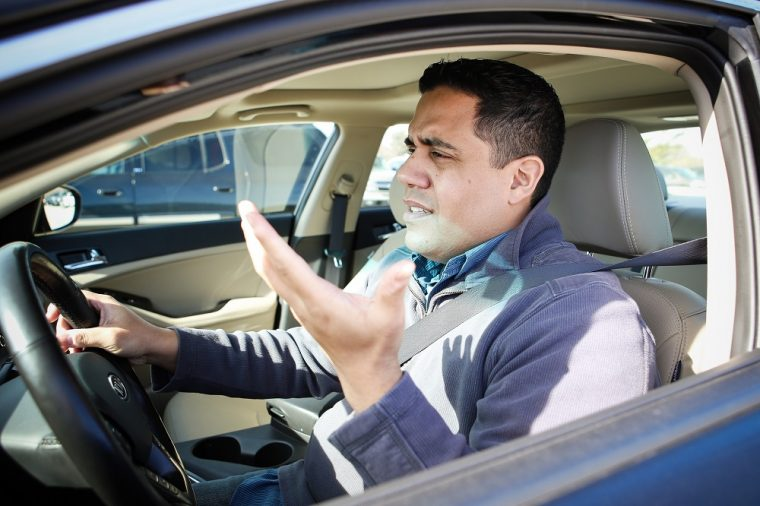 Male driver stuck in traffic and gesturing in a frustrated manner