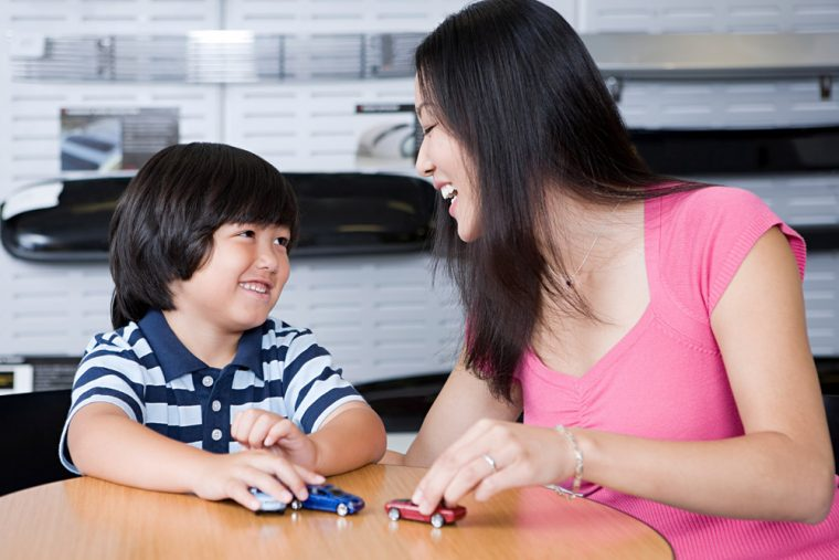 Mom and kid playing with toy cars