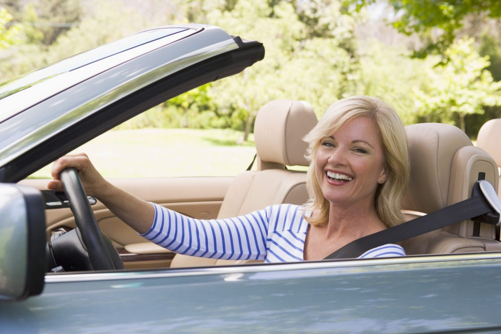 Blond woman with nice hair driving in a convertible on a sunny day
