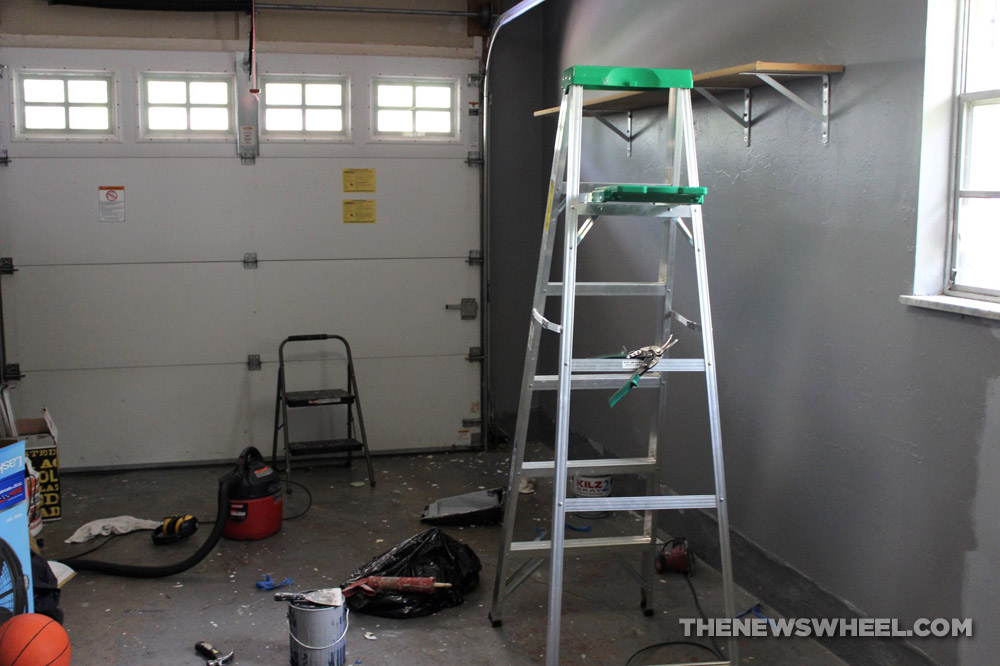 Interior of a garage with a  ladder, step-ladder, shop-vac, paint, scraper, boxes, and a basketball
