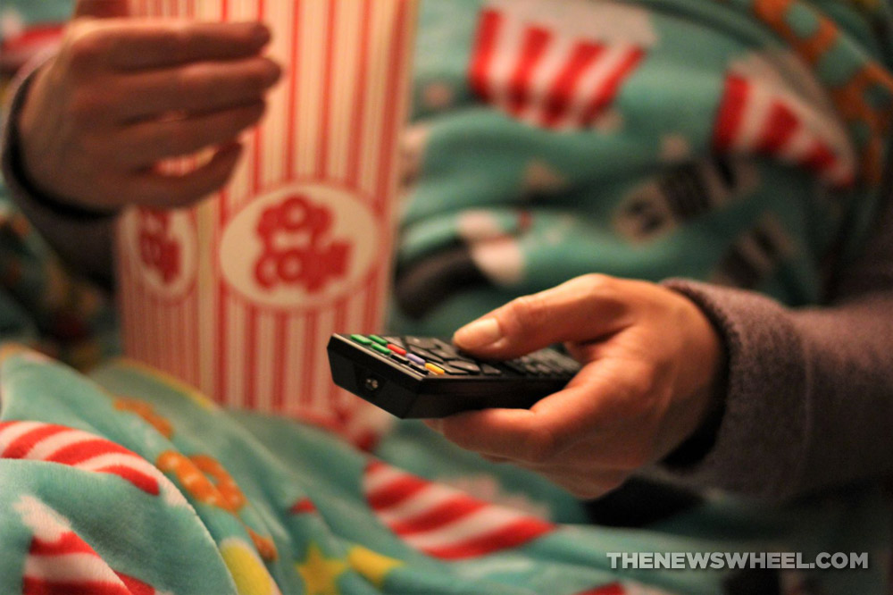 Person with remote control, a container of popcorn, and a blanket sitting on a chair or couch