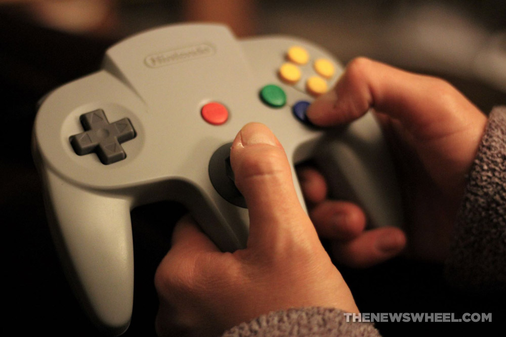 Person holding a video game controller for a Nintendo 64 retro console