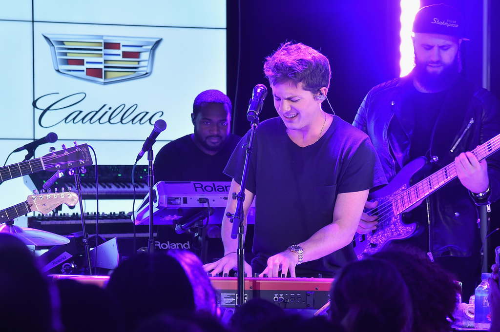 Charlie Puth performs on the keyboard while singing at the Globa
