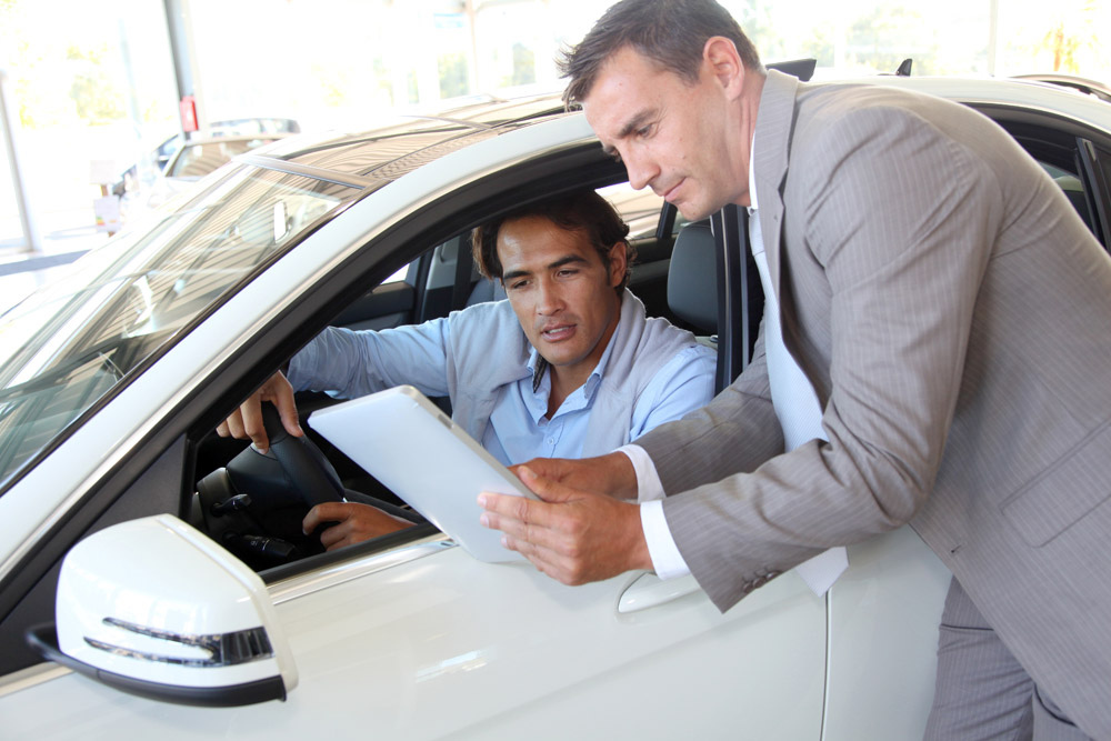 car salesman on the job at a dealership selling cars to a shopper in a vehicle