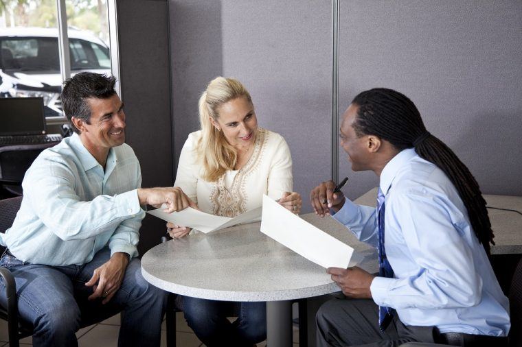 couple signing paperwork at dealership