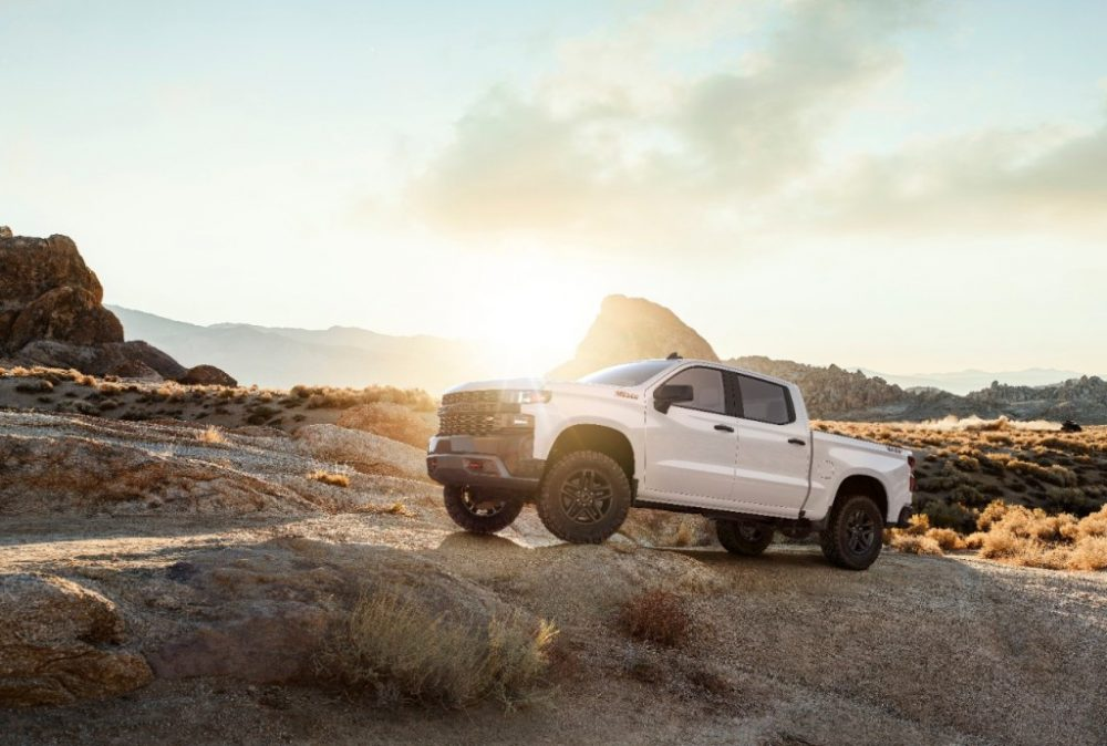 2019 Chevrolet Silverado 1500 parked off-road in the desert with the sun in the background