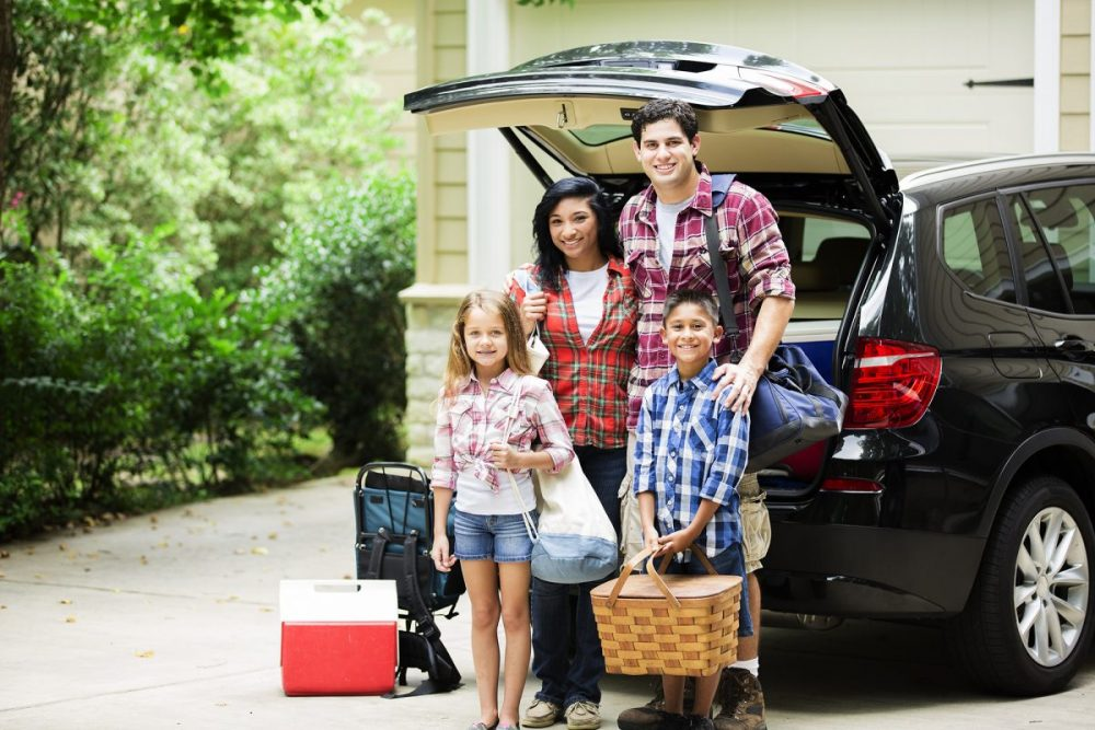 Family standing in front of an SUV with an open trunk, surrounded by luggage for a road trip