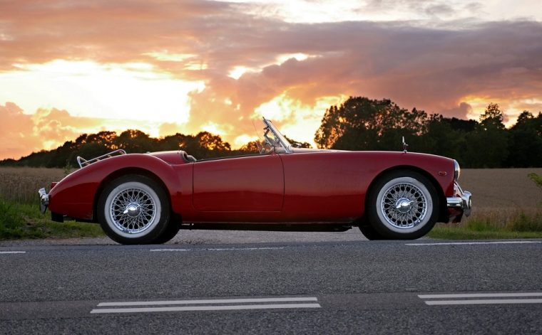 classic red convertible car at sunset