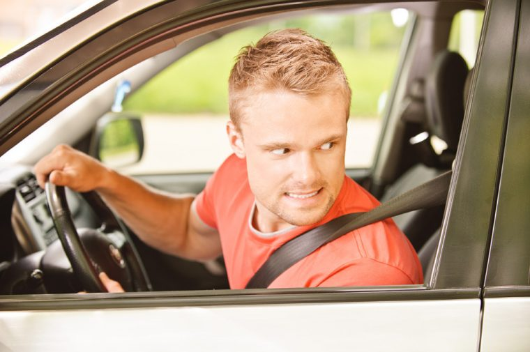 Worried, scared man looking backward while driving with anxiety