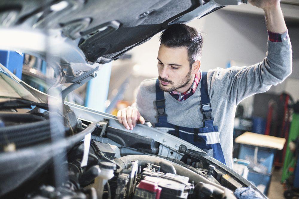 Mechanic inspecting a car under the hood