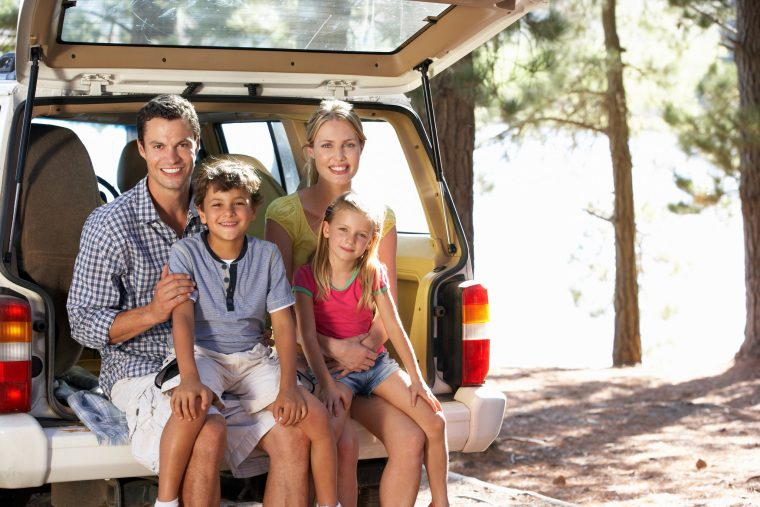 smiling family sitting in back of car