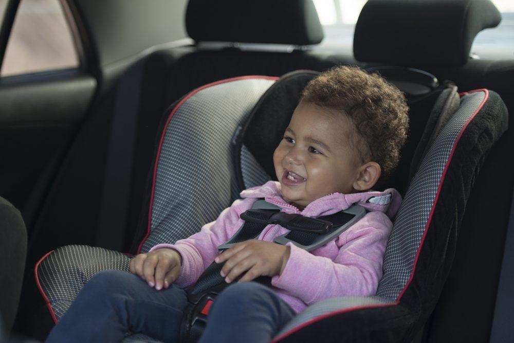 smiling kid in car seat