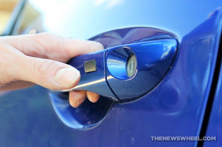 A hand grabbing a blue car door handle
