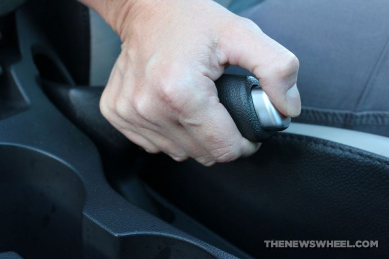 Person engaging emergency or parking brake in a car