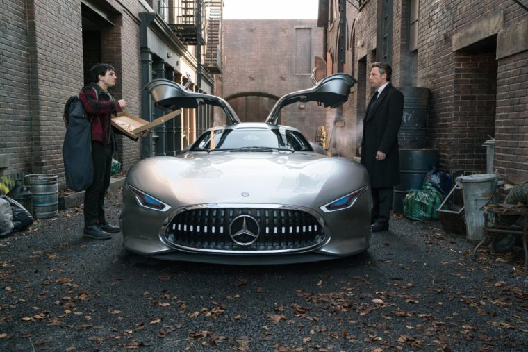 Ben Affleck and Ezra Miller standing on either side of a new Mercedes-Benz in the film Justice League