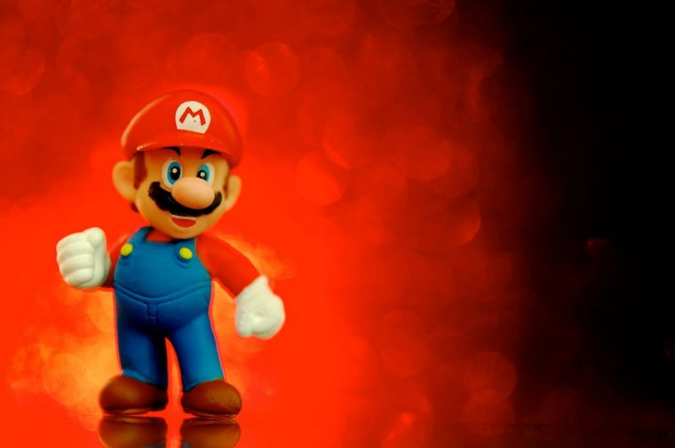 Mario standing in front of a red backlight, looking smug.