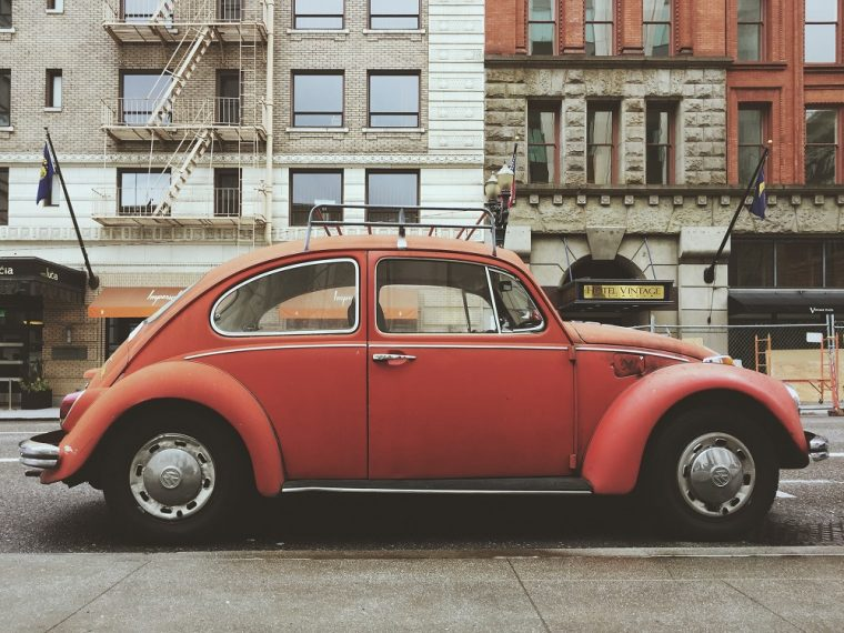 A red VW Beetle parked on a city street.