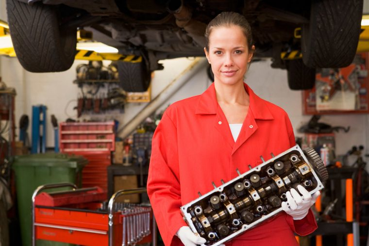 female mechanic holding a car part with an elevated vehicle in the background