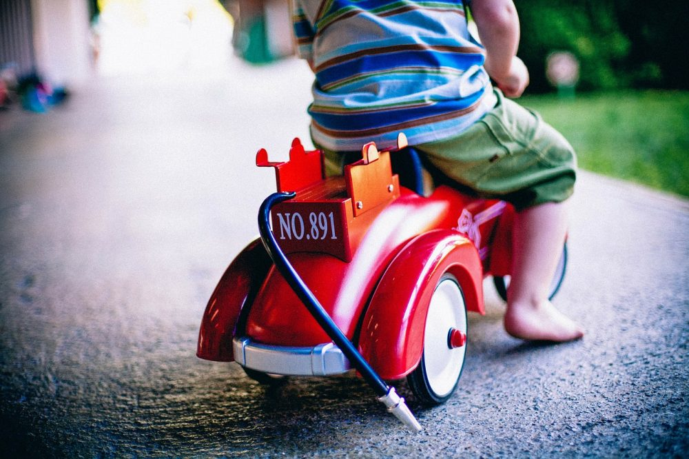 Kid riding on a on toy push Car