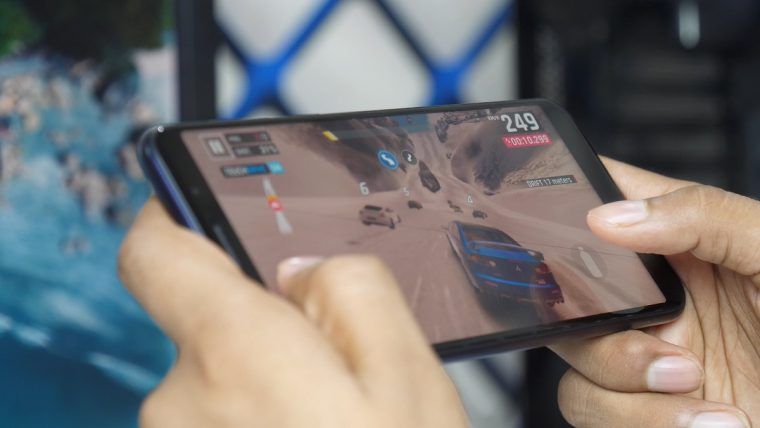 A smartphone playing a racing game