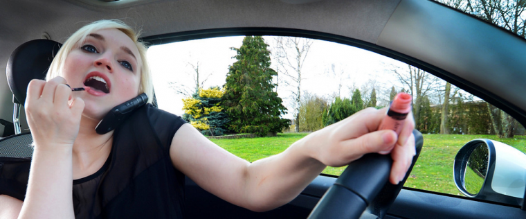 woman applying makeup while driving distracted