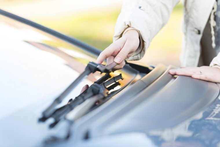 Woman's hand picking up windshield wiper