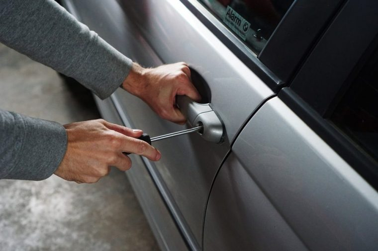 Person using a screwdriver to break into a grey vehicle