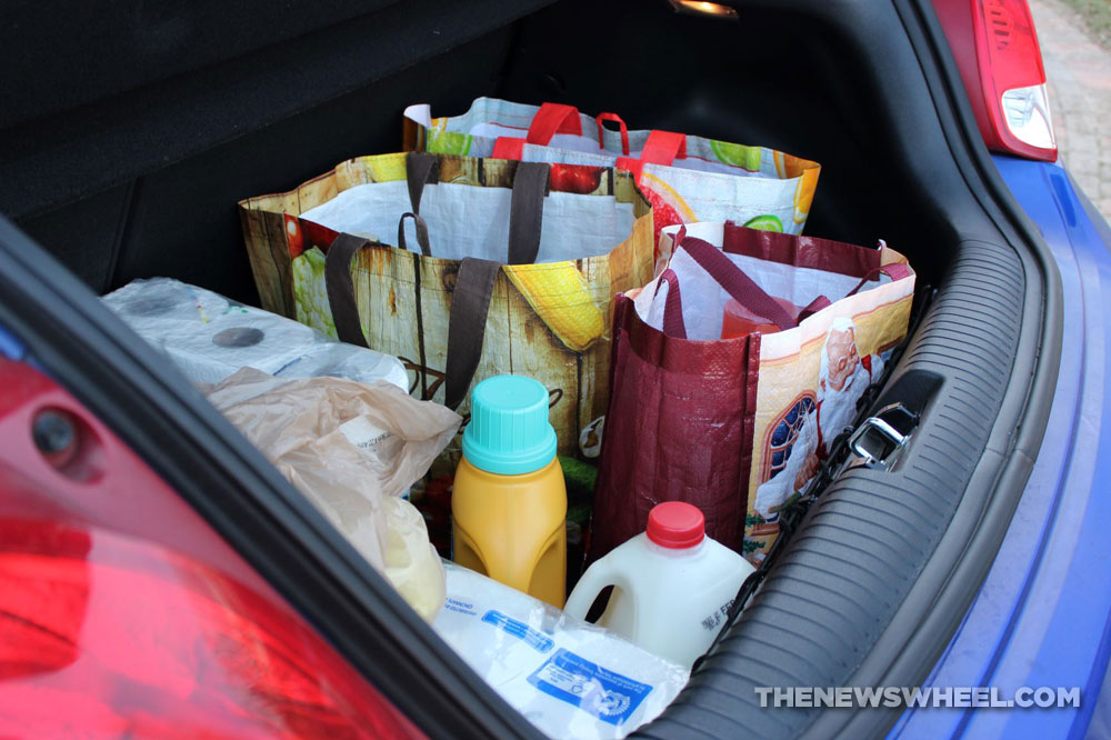 Trunk filled with bags of junk, bottles, groceries