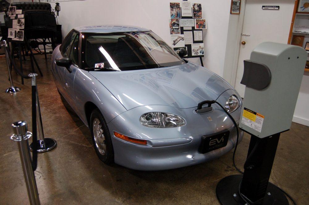 A gray GM EV1 at a charging station