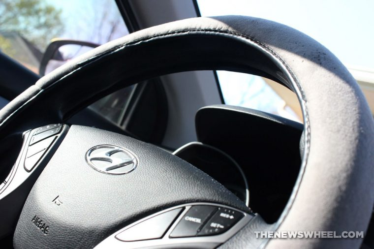 Black steering wheel with Hyundai logo and cloth cover