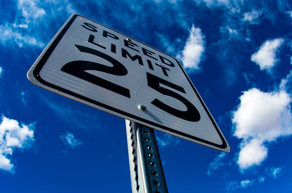 25 MPH speed limit sign taken from below with blue cloudy sky in background