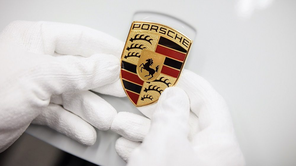 Hands place a Porsche crest on a Porsche 911