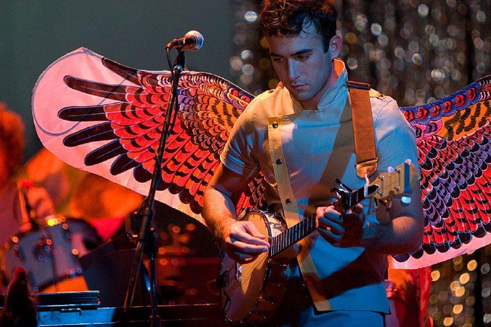 Sufjan Stevens playing Banjo while wearing wings for some reason