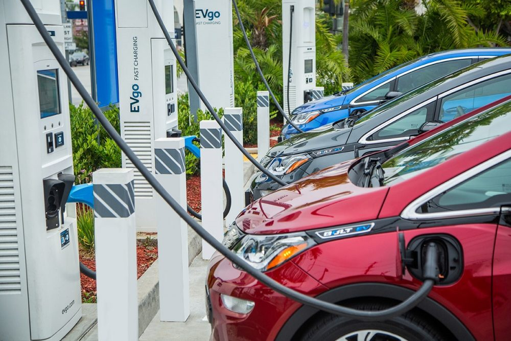 Three Chevy Bolt EVs lined up and getting charged at charging stations