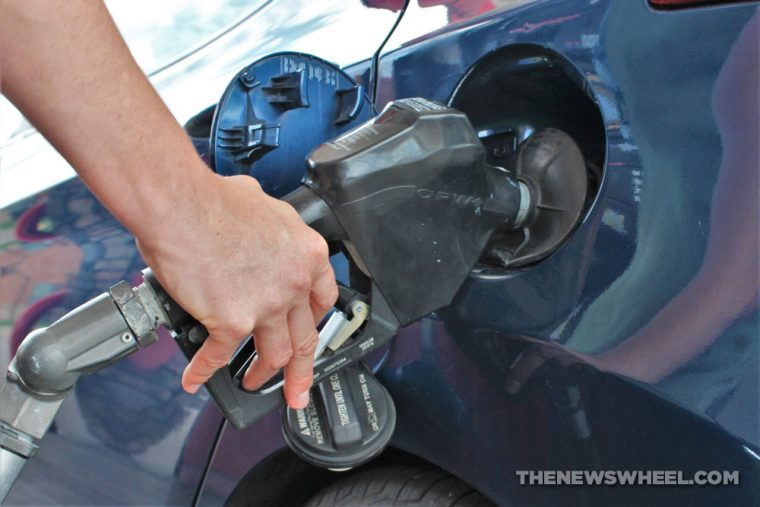 gas pump nozzle filling up vehicle tank