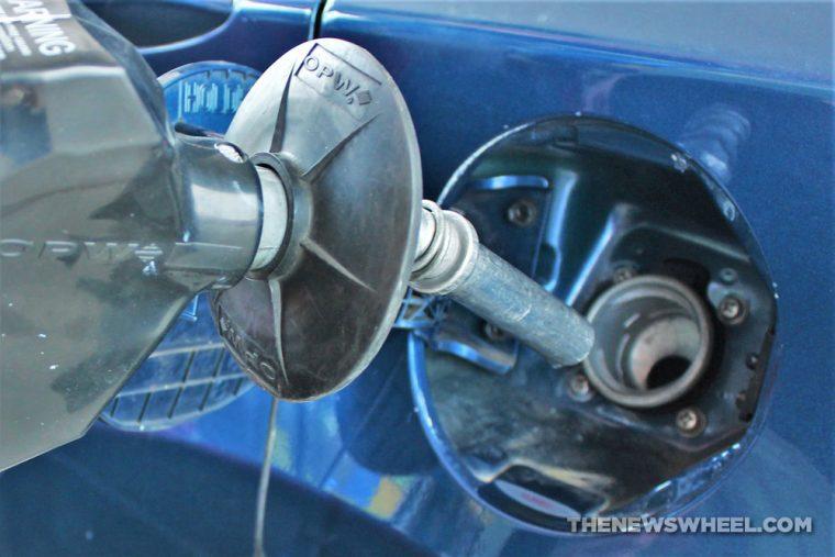 gasoline pump entering a blue car's fuel tank at a gas station