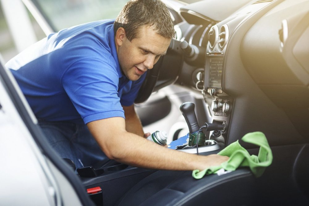 man cleaning interior of vehicle seats