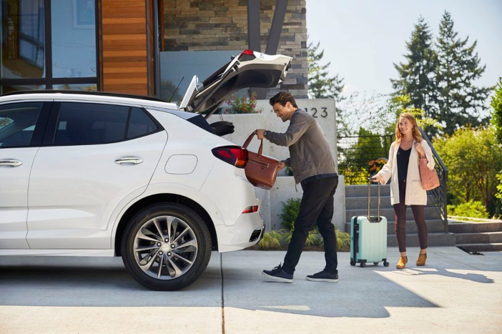A man and woman bringing luggage from a house to the 2020 Buick Encore GX